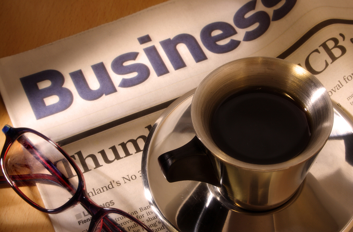Image of a cup of coffee on top of the business section of a newspaper